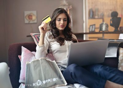 Woman holding credit card shopping online on her laptop